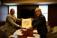 山極総長にアフリカ同窓会の記念バッグを渡すバヘタ部門長